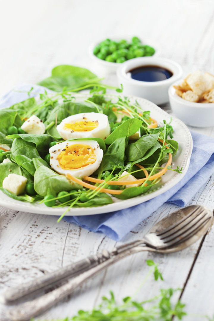 Fresh summer salad with green beans, spinach leaves and eggs on white wooden background, selective focus