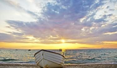Lonely fishing boat at the seashore on sand. Beautiful sunrise