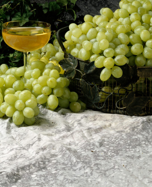 Bunch of grapes near a glass of wine