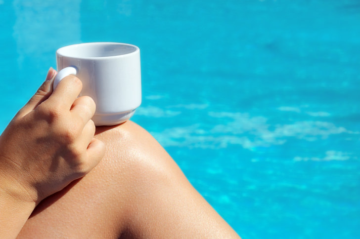 Closeup image of real attractive female beauty holding cup of coffee