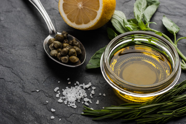 Olive oil  with lemon , capers and different greens