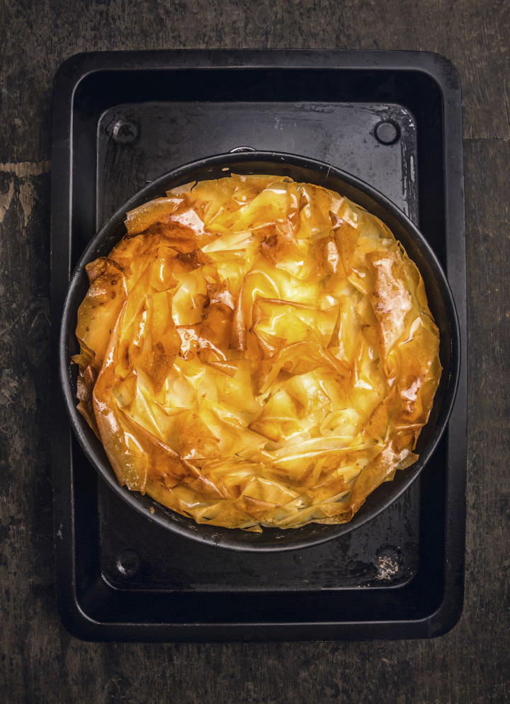 golden Filo pastry pie on black baking tray, top view