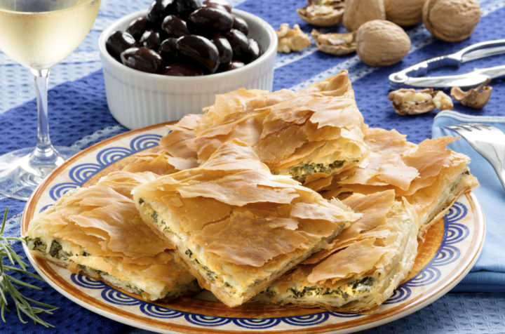 Spanakopita, Greek spinach pie with feta cheese and filo party on on plate with Greek white wine, olives and walnuts