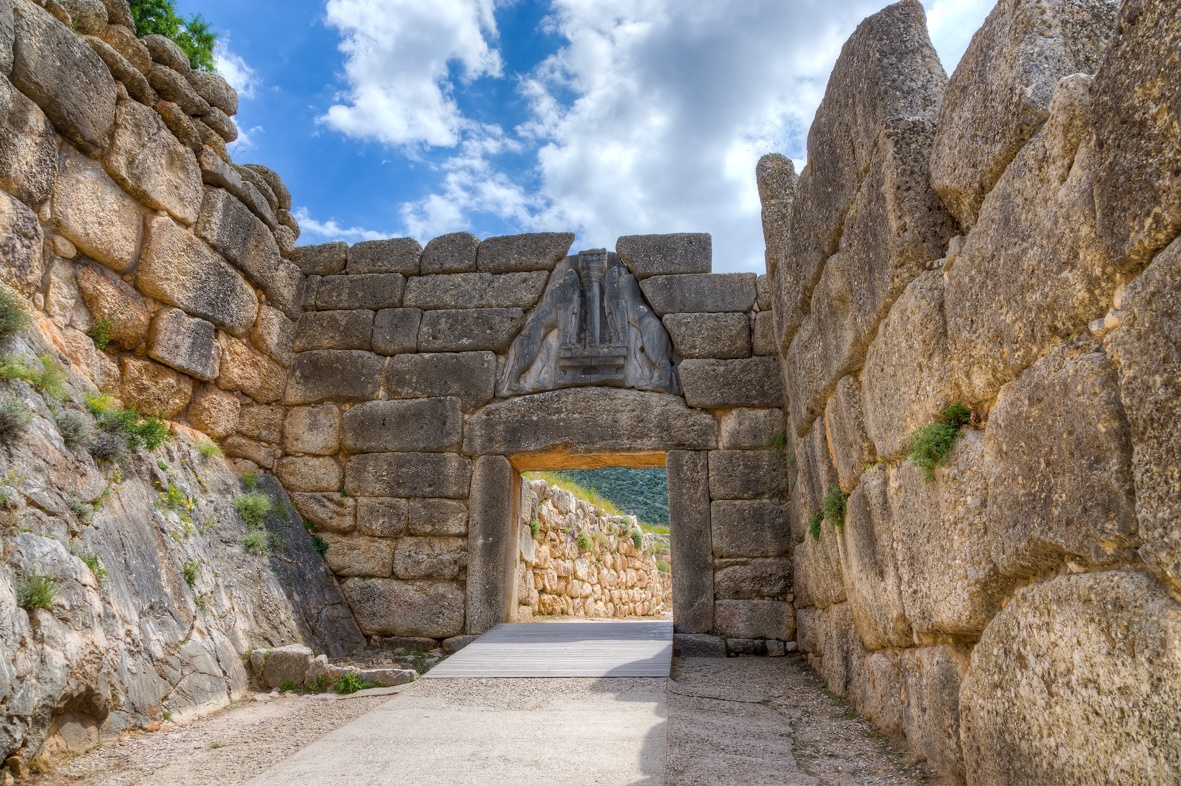The Lion Gate was the main entrance of the Bronze Age citadel of Mycenae, southern Greece. It was erected during the 13th century BC in the northwest side of the acropolis and is named after the relief sculpture of two lionesses in a heraldic pose that stands above the entrance. The Lion Gate is the sole surviving monumental piece of Mycenaean sculpture, as well as the largest sculpture in the prehistoric Aegean.