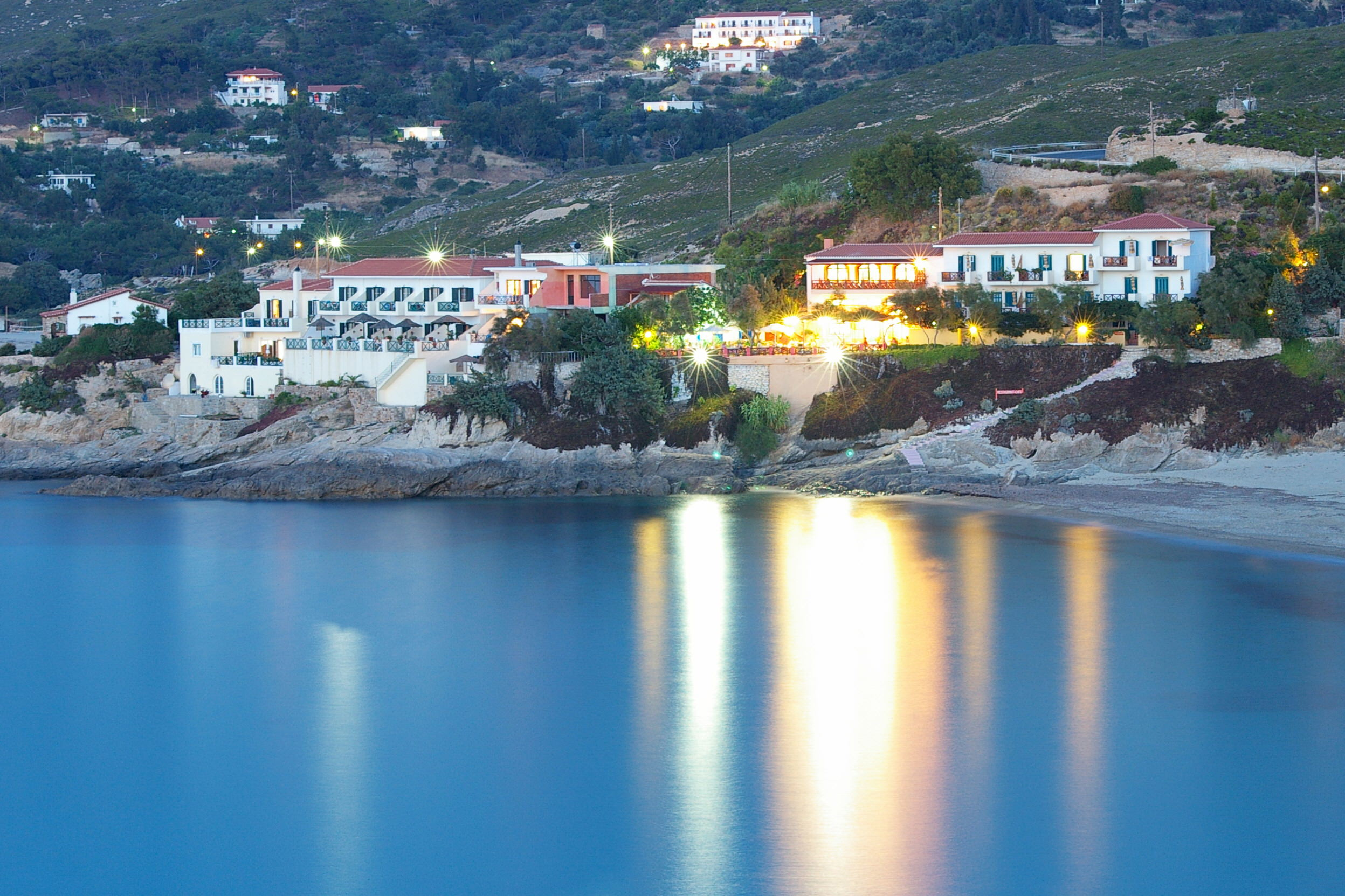 A beautiful Greek village by night and the reflection in the Aegean sea