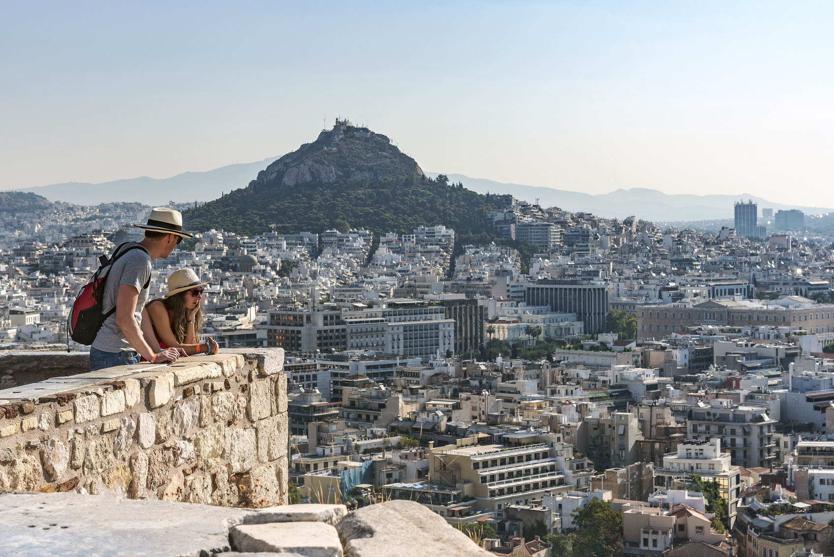 Athens, Greece - August 16, 2015: Two tourists look at panorama of Athens and Licabetus hill fro walls of Acropolis.