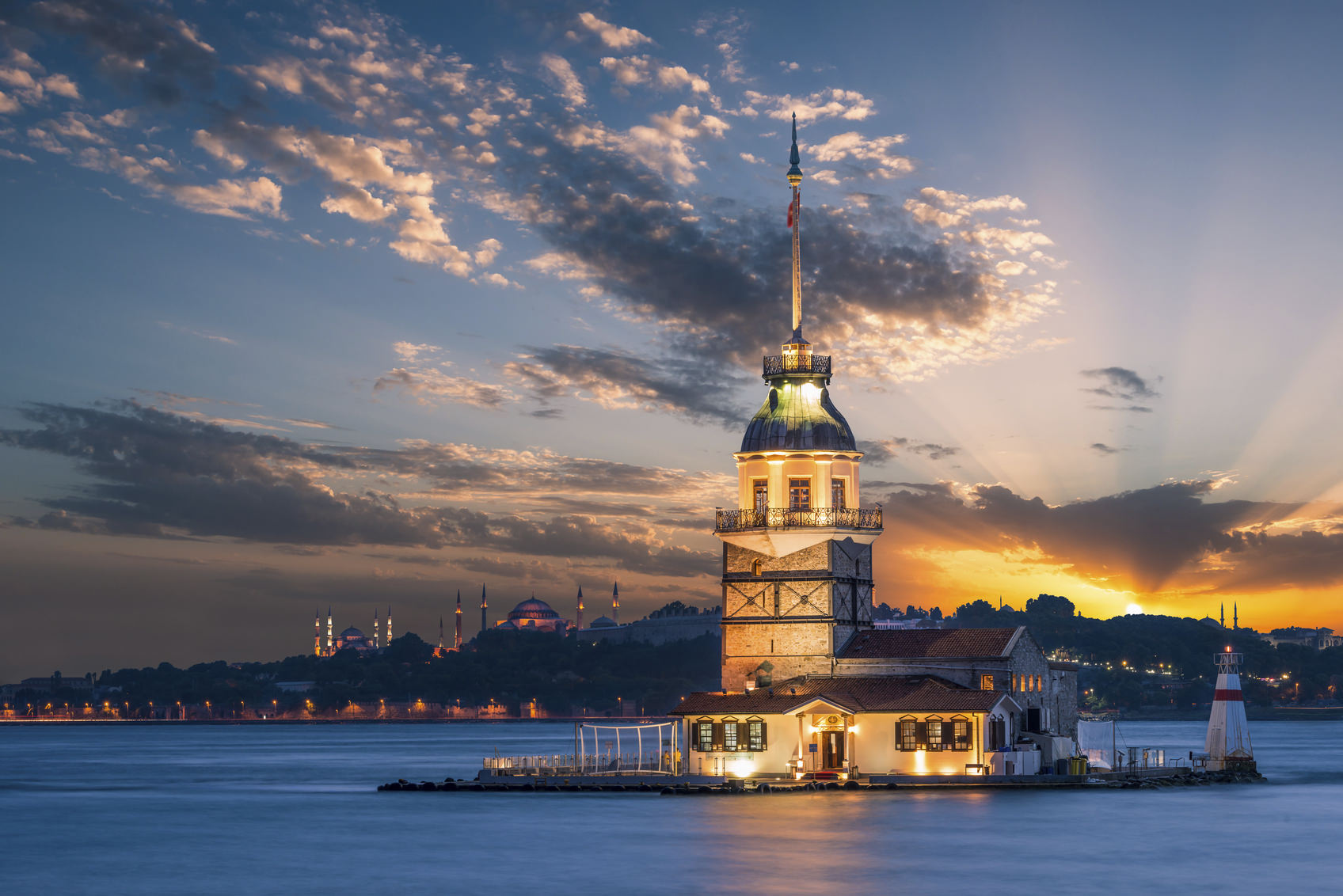 Maiden's Tower lit up in early evening, with the Hagia Sophia and the Blue Mosque in the far distance.