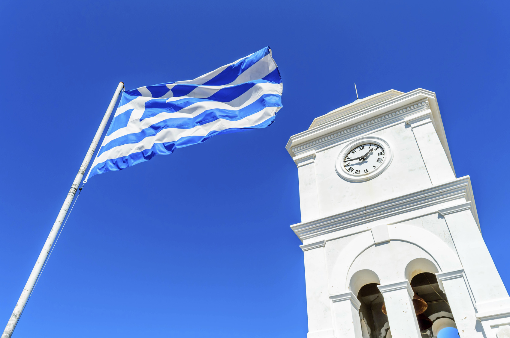 Poros, Greece - 03 October, 2015: The Clock tower of Poros Island in Greece with the Greek flag.