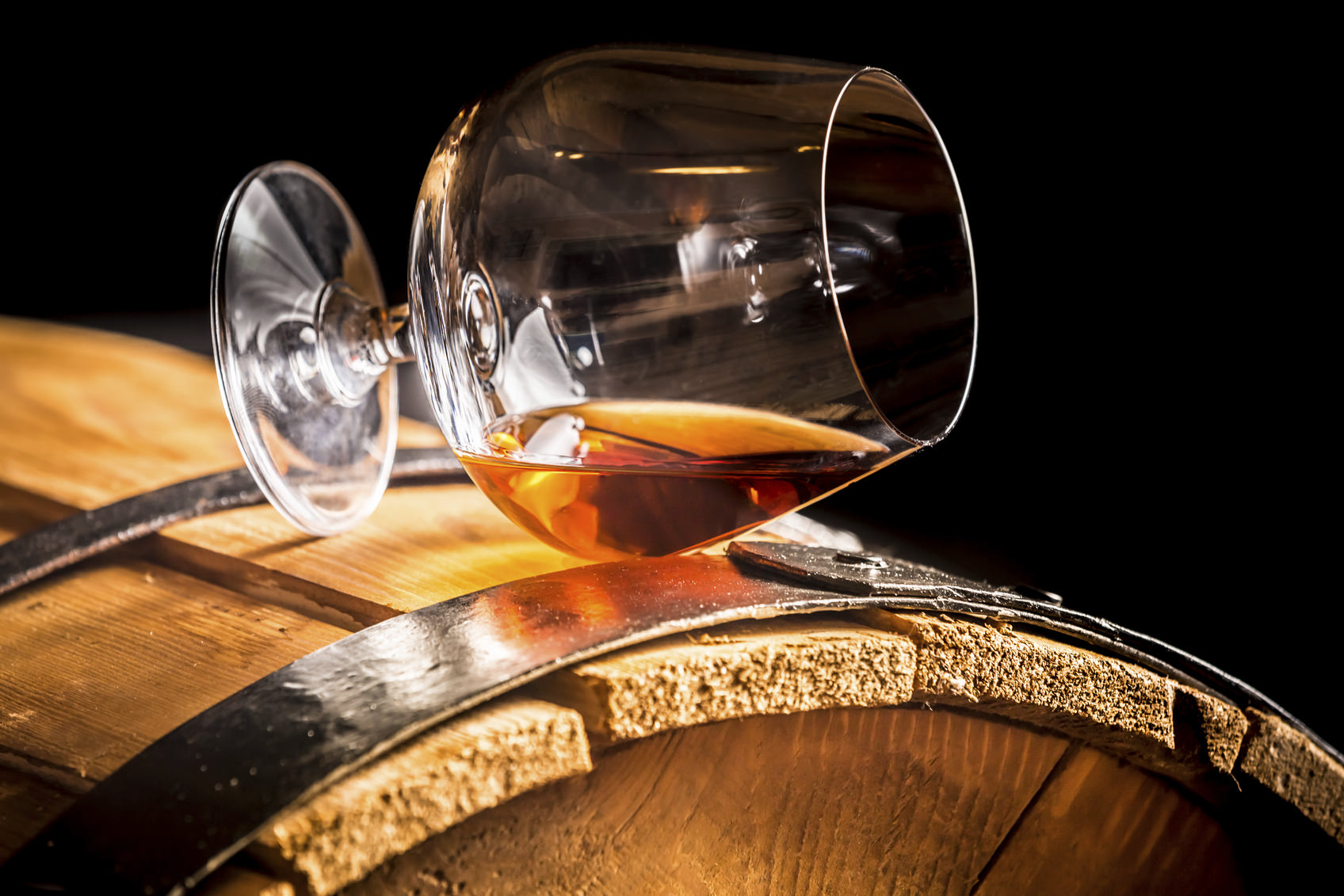 Glass of cognac on the vintage wooden barrel.