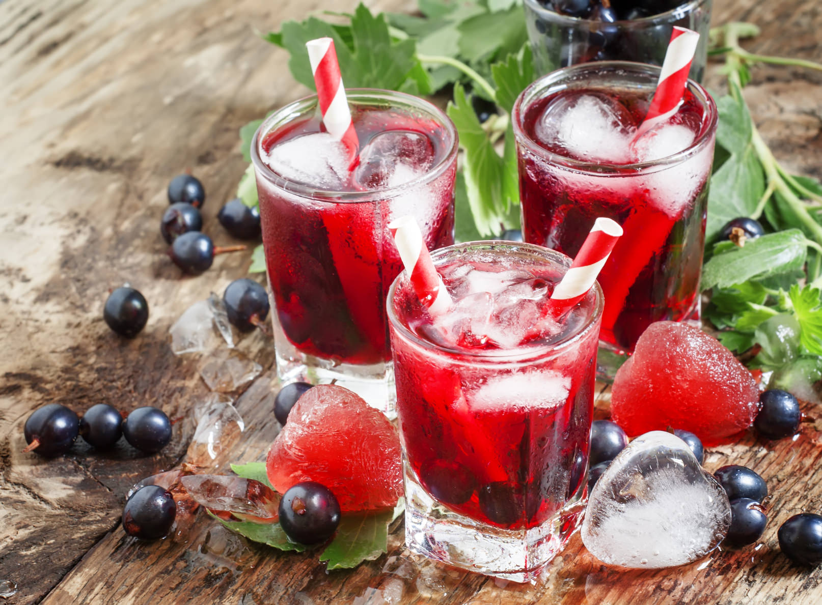 Fresh blackcurrant drink with berries and ice in a heart shape, selective focus