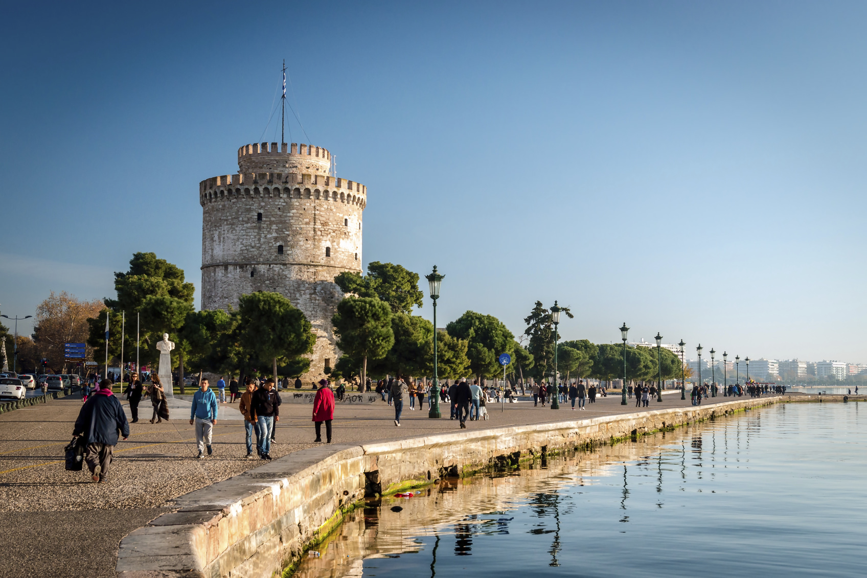 Thessaloniki, Greece - December 24, 2015: People walking on the coast in Thessaloniki next to the white tower which once guarded the eastern end of the city's sea walls