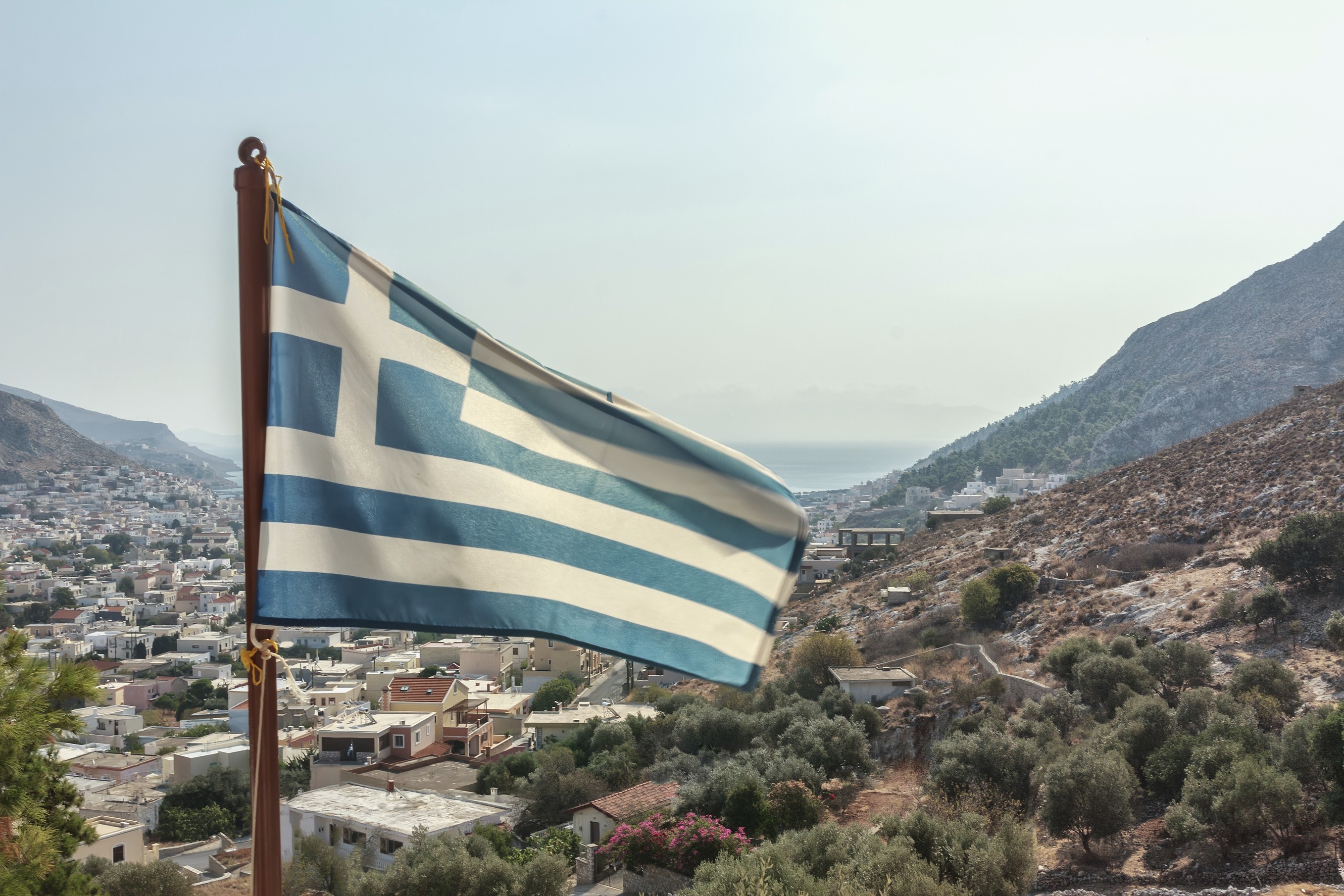 Flag of Greece is waving at Pothia cityscape the capital of Kalymnos island background