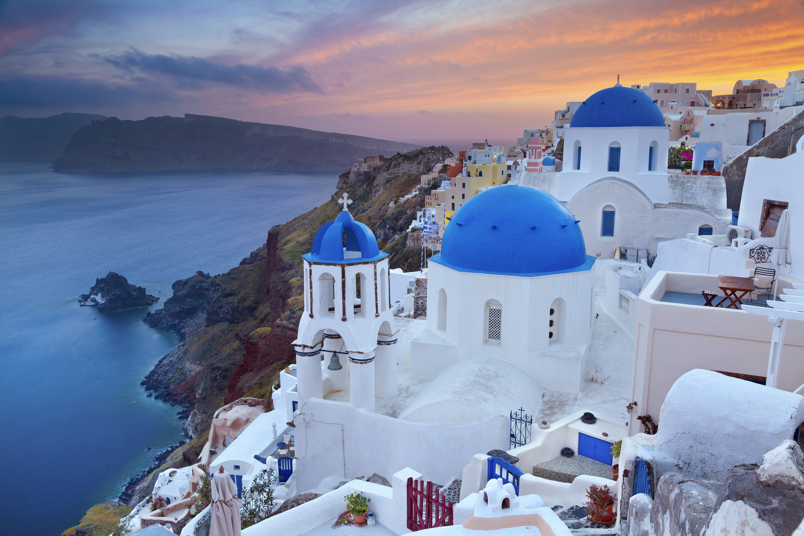 Image of small village Oia, located on beautiful greek island Santorini, during sunset.