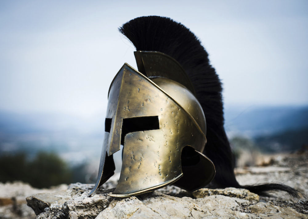 Spartan helmet with black crest on rocks.